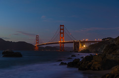 Golden & Purple (Ash and Debris) Tags: stone rock usa calm purple bay city southbay silence evening stones rocks lights california blue urban sanfrancisco bridge goldengate illumination waves sky goldengatebridge unitedstates night water light