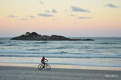 Solitary ride (Maria Luiza S) Tags: byke island sundown sea beach ocean sky man
