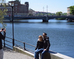 Can you please take a picture of us? (lucasual) Tags: sweden stockholm picture photograph tourists architecture bridge river man woman sun smartphone sunglasses smile couple