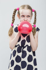 Portrait of Funny Caucasian Blond Girl With Pigtails Posing in Polka Dot Dress Against White. Blowing Up Red Heart Shaped Air Balloon. (DmitryMorgan) Tags: 1 710years adorable airballoon baby beautiful blond blowup caucasian cheerful child childhood daughter dress european expression female fun girl heartformed holding human inflate joy kid little love model mood one pigtails polkadot portrait positive preschooler school schoolgirl small smile smiling straw studio white young