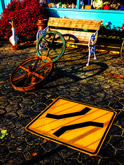 A Wheely Narrow Bridge (Steve Taylor (Photography)) Tags: sign bench seat shop bird goose yellow blue black red brown green metal wood newzealand nz southisland canterbury christchurch plant bush perspective wheel narrowbridge
