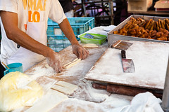 Man cooks youtiao at the street market (Evgeny Ermakov) Tags: asia asian chinese chinesecruller georgetown malaysia penang breadstick candid closeup cook cooking cruller cuisine culture donut dough doughnut famous food hand hands market marketstall marketplace stall stick street traditional typical vendor work youtiao editorialuse