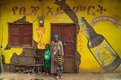 Ethiopian family standing in front of an old beer advertising painted on a wall, Omo valley, Jinka, Ethiopia (Eric Lafforgue) Tags: abyssinia advertising africa african alcohol art artistic beer blackskin children colourimage day door eastafrica ethiopia ethiopia0617539 ethiopianethnicity fulllenght horizontal hornofafrica jinka lookingatcamera mother multicoloured mural muralpainting omovalley outdoors painted paintedwall painting pattern portrait poverty saintgeorge threepeople travel typical wall wallpainting