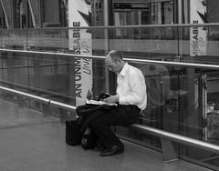 Waiting and working (alsib) Tags: blackandwhite station working waiting man work trainstation streetphotography fujifilmxt2 london stpancras