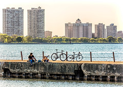 Hangin' Out (Wes Iversen) Tags: chicago fencefriday hff illinois lakemichigan montrosepier montrosepoint tamron150600mm apartments architecture bicycles bikes cities cityscape decay fences people piers trees water