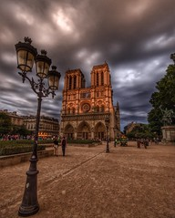 Notre Dame cathedral is picked out by the setting sun again not a backdrop of ominous clouds (alcowp) Tags: tourism sunset clouds architecture parvis notredame religion cathedral cathedrale paris france