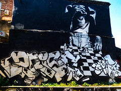 Whose Move Next;  Mine or Man's (Steve Taylor (Photography)) Tags: art graffiti mural streetart building black blue brown green lowkey contrast uk england london weeds tag wall chimpanzee ape monkey trousers chess board pondering trafficgraphics 2rise