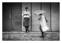 Far Away, So Close (Dave Fieldhouse Photography) Tags: monochrome mono blackandwhite birmingham street streetphotography umbrella rain doorway people cobbles cobblestones chef texting fujifilm fuji fujixpro2 fujinon35mmf2 wwwdavefieldhousephotographycom project