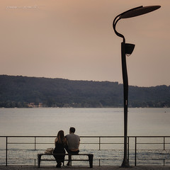 romanticherie (pamo67) Tags: pamo67 romance coppia pair lago lake lampione lamp 2 two seduti seated lungolago lakefront panchina bench square pomeriggio lateaftermoon pasqualemozzillo