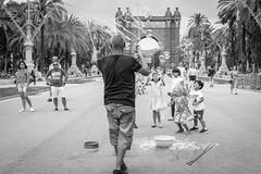 Bubbles, Street Photography in Barcelona (Geraint Rowland Photography) Tags: streetphotography streetportraits streetentertainer streetphotographytours streetphotographergeraintrowland arcdetriomf barcelona espana spain catalonia blackandwhite architectureinbarcelona parks openspaces children bubbles fun
