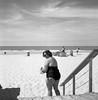 "Oostende (Sailing ""Footprints: Real to Reel"" (Ronn ashore)) Tags: woman beach sand people portrait environmentalportrait bw blackandwhite 500x500 6x6 tlr rolleiflextlr28f carlzeissplanar80mmf28 square classiccamera twinlensreflex ilfordhp5inxtol milford horizon oostende seaside"