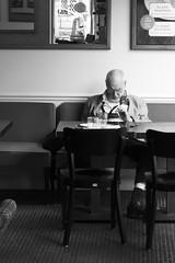 Busy (Ren-s) Tags: noiretblanc noir noirblanc blanc blackandwhite black blackwhite white monochrome contrast contraste grey gris bw belgique belgium bruxelles brussels europe street streetphotography photographiederue people personne homme man phone gsm téléphone portable olympusm1442mmf3556iir olympus café coffee shop table chaises chairs canapé old vieux