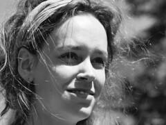 Smile (d_t_vos) Tags: smile girl woman youngwoman teenager teen hair sun sunny sunnyday ribbon headband hairribbon fillet smiling dof contrast monochrome gleam radiate beam glow glisten shine street streetphotography streetportrait candid curl flourish ringlet zwartwit zw bw curling leeuwarden eewal hofplein grotehoogstraat kleinehoogstraat straatfestival dickvos dtvos