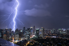 The heavens explode (Sumarie Slabber) Tags: lightningstrikes manila philippines weather nightphotography flickr google sumarieslabber stormyweather clouds cloudy stormchaser skyscrapers ligts reflection thunder bolts epic sky night skyline architecture