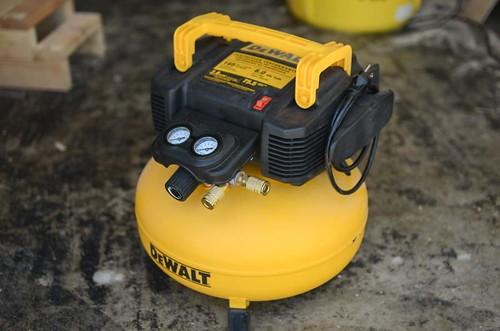 yelllow Dewalt air compressor on concrete floor