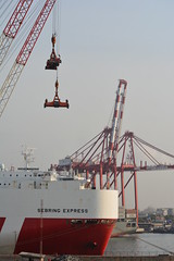 THE LARGE CARGO SHIP CALLED SEBRING EXPRESS BEING LOADED IN THE PORT OF LOME, TOGO,  AFRICA (vermillion$baby) Tags: africa boat containers crane done flickr freighter green lome red ship togo vessel wharf workboat ocean sea westafrica togosea port containor atlantic atlanticocean workboats cranef dock container cargo transportation pier wharves international world