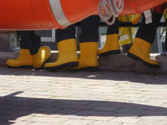 Life boots (Nekoglyph) Tags: whitby yorkshire rnli wellies rubber boots black orange yellow lifeboats shadows fence draped wetsuits drying