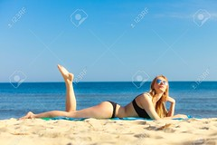 51781700-Summer-vacation-Sexy-girl-in-bikini-sunbathing-tanning-on-the-beach-Young-woman-relaxing-on-the-sea--Stock-Photo.jpg