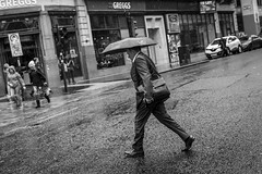 Wet Wet Wet (Leanne Boulton) Tags: monochrome people urban street candid streetphotography candidstreetphotography streetlife dutchangle man male businessman walking stride motion movement road wet weather rain raining shower suit umbrella tone texture detail depth naturallight outdoor light shade shadow city scene human life living humanity society culture canon canon5d 5dmkiii 50mm ef2470mmf28liiusm black white blackwhite bw mono blackandwhite glasgow scotland uk