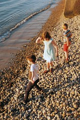 Skimming pebbles, Totland Bay (Chi Bellami) Tags: film fujifilm fujicolor c200 nikon nikonosv 35mm zonefocus scalefocus scanned scan colour c41 negative photohippo chibellami amphibiouscamera nikonos totland totlandbay beach shore coast pebbles sea isleofwight oliver family