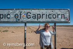Tourists pose in front of the Tropic of Capricorn sign in the Namib desert, located in Namibia, Africa. The Tropic of Capricorn is part of a world map that indicates the division between the southern temperate zone and northern tropics. (Remsberg Photos) Tags: africa namibia world namib desert tourist photographing pose happy smile exoticlocation sign tropicofcapricorn capricorn landmark worldmap solitaire nam