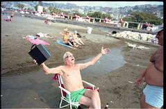 (The Spirit of the Radio) (Robbie McIntosh) Tags: leicamp leica mp rangefinder streetphotography 35mm film pellicola analog analogue negative leicam elmarit analogico leicaelmarit28mmf28iii elmarit28mmf28iii dyi selfdeveloped filmisnotdead autaut candid bellinifotoc41 kodakportra160 kodakportra portra kodak beach tan seaside bathers strangers swimsuit lidomappatella mappatellabeach singer man radio belly