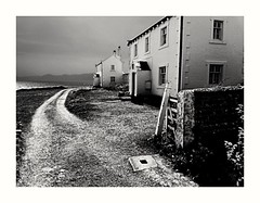 Penmon (Develew) Tags: penmon anglesey wales northwales sea seashore coast coastline houses whitewash whitewashedhouses olympus epl3 olympusepl3 gate gatepost gateway path pathway coastalpath cottages lighthousekeeperscottages roadway track sunlight mountains shadows viewpoint blackandwhite bw monochrome