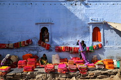 Selling Colors (Alex L'aventurier,) Tags: jodhpur inde india bluecity villebleue candid windows fenêtres orange sari saree clothe clothing street rue urbain urban rajasthan dog chien people personne fabrics