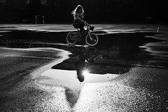 after the rain (igo.rs) Tags: girl street water reflection sun black white bicycle female child children kid bike childhood joy driving playong