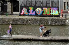 Alone with the Family (Canis Major) Tags: bristol harbourside arnolfini family pushchair water alone mural letters