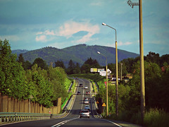 road to the mountains (Ola 竜) Tags: road highway mountain hill highpov cars drive mountains green trees lamps street blue sky cloud warmtones focus fz200 perspective
