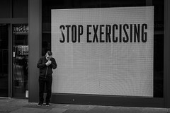 Stop Exercising (Leanne Boulton) Tags: monochrome urban street candid portrait streetphotography candidstreetphotography candidportrait streetlife juxtaposition juxta humour humorous fun funny message text man male face smoke smoker smoking cigarette window store display screen tone texture detail depth naturallight outdoor light shade shadow city scene human life living humanity society culture canon canon5d 5dmarkiii ef2470mmf28liiusm black white blackwhite bw mono blackandwhite glasgow scotland uk