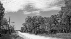 Main Street, Harlan, Kansas (unknown quantity) Tags: trees monochrome dirtroad abandonedbusiness utilitypoles sky clouds horizon sign grass blackandwhite weathered brokenroof shadows wires cloudsstormssunsetssunrises