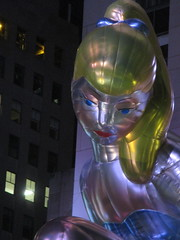 Seated Ballerina Mylar Balloon at Night 6237 (Brechtbug) Tags: seated ballerina mylar balloon night art sculpture by jeff koons 2017 rockefeller center nyc 30 rock new york city standing up above ice rink gold prometheus statue giant decoration ornaments 05202017 nights nite nites lights lites light oversize load ornament summer spring kids toy kitsch 60s toys sculptures statues pretty evening lobby plaza plant plants plastic artist
