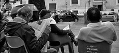 Reading club. (Baz 120) Tags: candid candidstreet candidportrait city candidface candidphotography contrast street streetphoto streetcandid streetphotography streetphotograph streetportrait rome roma romepeople romestreets romecandid europe monochrome monotone mono blackandwhite bw noiretblanc urban voigtlandercolorskopar21mmf40 voightlander leicam8 leica life primelens portrait people unposed italy italia grittystreetphotography faces decisivemoment strangers