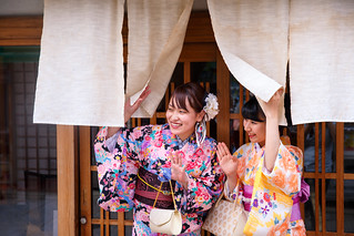Young Kimono women saying hello in front of Japanese restaurant