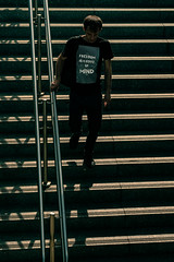 Freedom is a state of mind. (stray_light_rays) Tags: warsaw street streetphotography contrast stairs rail shirt slogan guy walking shadow dark goingdown silhouette man