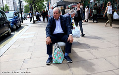 `1978 (roll the dice) Tags: london westminster westend w1 oxfordstreet sale bargain bag fashion shops shopping streetphotography taxi hot sunny people natural bored sad mad emotion wisdom old uk art classic england urban portrait traffic candid stranger husband pose kneesc tourism man canon londonist unaware headphones relax sit afternoon brave reaction