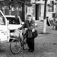 Resistant (Go-tea 郭天) Tags: qingdao man old guy grandpa coat bag cars bicycle bike ride riding push pyshing move movement moving glasses cap wrinkles ages sport exercice power basket alone lonely strong canon eos 100d 50mm prime street urban city outside outdoor people bw bnw black white blackwhite blackandwhite monochrome naturallight natural light asia asian china chinese shandong good spirit clean green transport transportation candid portrait