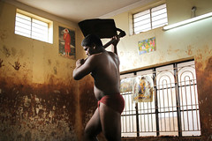 Indian mud wrestlers (slow paths images) Tags: india southasia indiansubcontinent southindia karnataka mysore kushti kusti indianmudwrestler pehlwani sports tradition akhara school man indian wall windows lowllight neonlight sirdi saibaba poster indoors training exercise body travel