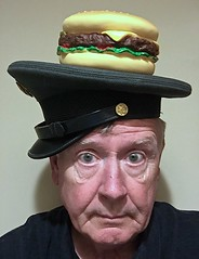 Self-Portrait Wearing Old Army Hat Sideways With Rubber Cheeseburger on Top (ricko) Tags: selfportrait hat armyhat cheeseburger rubber fake werehere