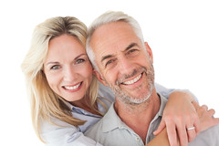 Close up portrait of happy mature couple (carolina dental center) Tags: 30s midadult woman female caucasian 50s matureadult man male closeup lookingatcamera whitebackground isolated cutout happiness casual smiling happy handsome attractive pretty beautiful leisure lifestyle couple together cheerful enjoyment fairhair blonde lighthair greyhair stubble portrait embracing hugging