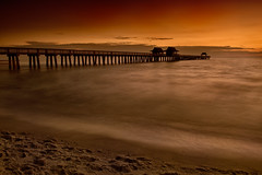 Sunset over the Naples Pier, Naples, Florida (diana_robinson) Tags: sunset naplespier naples florida woodenpier longexposure ocean gulfofmexico water smoothwater footprintsinsand sand sandybeach beach orangesky waves smoothwaves nikonflickraward
