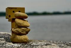 Cairn by Danbo (Tom Slate) Tags: danbo danboard cairn stackedstones yotsuba revoltech cardbo danboardfigure kiyohikoazuma kaiyodo bokeh water river pebblestack pebblebalancing balancingstones macro