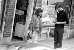 h31-68 32 (ndpa / s. lundeen, archivist) Tags: nick dewolf nickdewolf bw blackwhite photographbynickdewolf film monochrome blackandwhite city summer 1968 1960s 35mm boston massachusetts candid streetphotography citylife streetlife people beaconhill charlesstreet sidewalk pedestrian youngpeople pedestrians shop store storefront business window storewindow windowdisplay july saturday weekend july27 door woman youngwoman man youngman car vehicle automobile parkedcar 63charlesstreet hunters liquorstore liquor bottle bottles liquorbottle liquorbottles gilbeys gin glasses eyeglasses turtleneck brunette longhair sandals pipe pipesmoking pipesmoker poncho