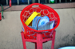 Draining the dishes (Roving I) Tags: plasticchairs baskets draining drying dishes cafes street danang vietnam plates