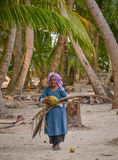 Elderly lady carrying a coconut