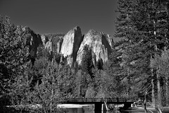 Swinging Bridge with a Backdrop of Cathedral Rocks and Spires (Black & White) (thor_mark ) Tags: blackwhite blueskies bridge capturenx2edited cathedralchimney cathedralrocks centralyosemitesierra colorefexpro day4 highercathedralrocks highercathedralspires hillsideoftrees landscape lookingsw lowercathedralrocks lowercathedralspires mercedriver middlecathedralrocks mountains mountainsindistance mountainsoffindistance nature nikond800e outside pacificranges pedestrianbridge project365 river sierranevada spiresgully swingingbridge trees triptopasoroblesandyosemite yosemitenationalpark yosemitevalley yosemiterittersierranevada california unitedstates