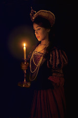 Let The Light Guide You (miriness) Tags: candlestick candlelight glow darkbackground tudor tudorqueen tudordress 1500s perioddrama bookcover bookcoverdesigner bookcoverartist commissioned model costumedesign costume oldfashioned film movie queen royal royalty pearls headdress lookingdown vintage retro caucasian availablelight light fire flame elegant regal oldpainting shadows reddress candelabra contemplating nighttime dark blackbackground f32 50mmlens