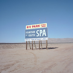 fountain of youth. salton sea, ca. 2016. (eyetwist) Tags: eyetwistkevinballuff eyetwist fountainofyouth spa sign billboard landscape empty saltonsea desert california ca111 mamiya 6mf 50mm kodak portra 160 mamiya6mf mamiya50mmf4l kodakportra160 ishootfilm analog analogue film mamiya6 square 6x6 mediumformat 120 filmexif iconla epsonv750pro lenstagger ishootkodak dirt sonorandesert dry bleak americantypologies imperialcounty roadsideamerica salton sea lonely desolate barren american west dead bombaybeach sand railroad tracks chocolatemountains type typography rvpark openallyear entrance arrow minimalism void vast